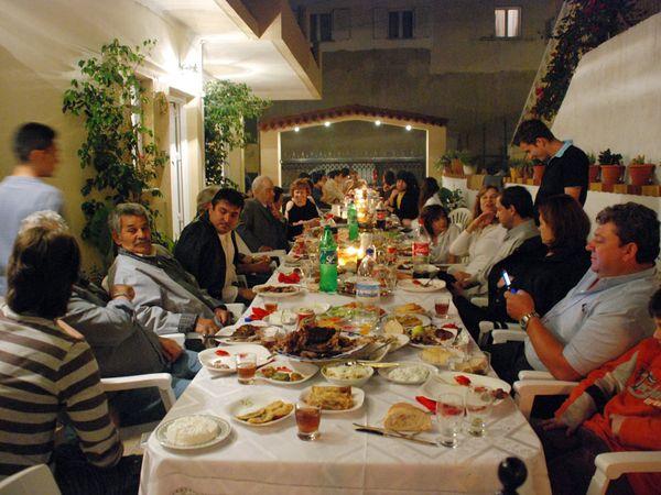 """Οικογενειακό δείπνο σε ένα σπίτι στην Κρήτη. Η φωτογραφία δείχνει του δύο πυλώνες του ελληνικού πολιτισμού: την τροφή και την οικογένεια. Παραδόξως, δεν υπάρχει η λέξη """"οικογένεια"""" στα αρχαία ελληνικά. Οίκος,είναι το πλησιέστερο συνώνυμο, που περικλείει την οικογένεια, την ιδιοκτησία, και τα ζώα."""