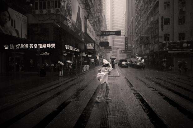 Μια καλοντυμένη κυρία προσπαθεί να διασχίσει το δρόμο υπό καταρρακτώδη βροχή.