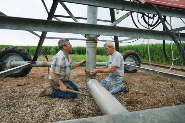 Αγρότες συνδέουν  σύστημα άρδευσης σε χωράφι με καλαμπόκια στην Ιντιάνα.