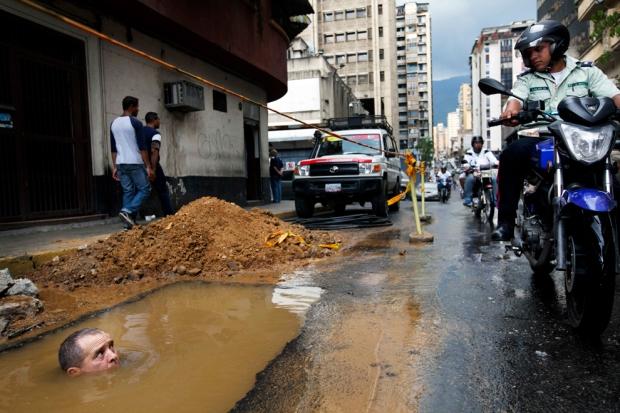 Εργαζόμενος προσπαθεί να επισκευάσει ένα σπασμένο σωλήνα στο Καράκας, Βενεζουέλα.