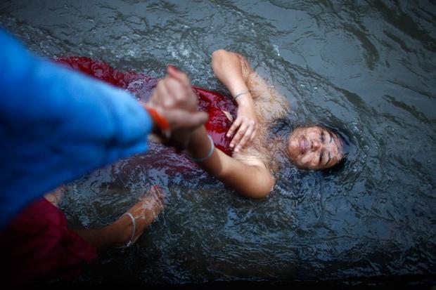 """μια """"ιερή βουτιά"""" στον ποταμό κατά τη διάρκεια της Bagmati Panchami , μια ημέρα καθαρισμού και εξιλέωσης  για τις γυναίκες, στο Κατμαντού, Νεπάλ,"""