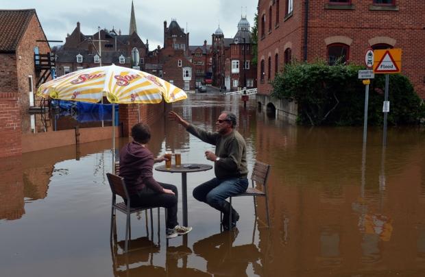 Ανδρες κάθονται στα νερά των πλημμυρών έξω από ένα μπαρ, καθώς τα επίπεδα του νερού συνεχίζουν να αυξάνονται στις όχθες του ποταμού Ouse στο York, βόρεια Αγγλία,