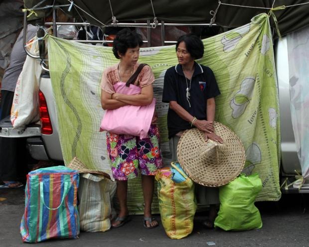 Δύο Ταϊλάνδέζες στέκονται δίπλα στις τσάντες τους γεμάτες με ξηρά τροφή κατά τη διάρκεια του Tae-Kra-Jard  στην Μπανγκόκ,