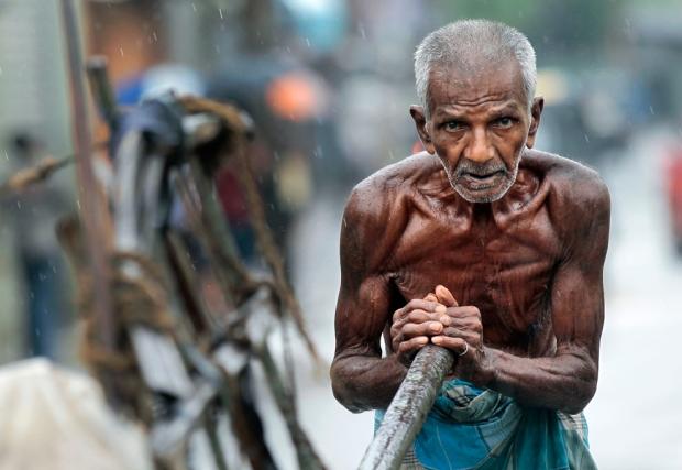 Ηλικιωμένος εργάτης σπρώχνει ένα καλάθι, καθώς βρέχει στο Κολόμπο, Σρι Λάνκα